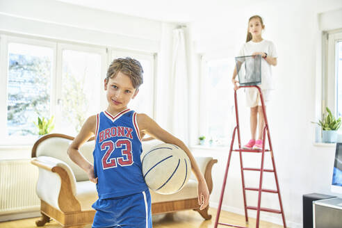 Portrait of boy and girl playing basketball in living room - DIKF00396