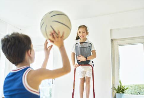 Boy and girl playing basketball at home - DIKF00399