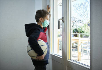 Sad boy with basketball and mask looking out of window - DIKF00405
