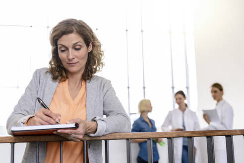 Businesswoman taking notes with female doctors in background - BMOF00358