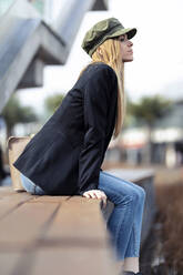 Blond young woman relaxing on a bench - JSRF00952