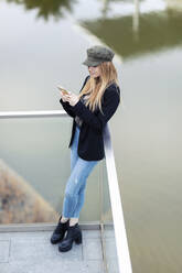 Blond young woman standing on terrace in front of water looking at cell phone - JSRF00955