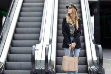 Portrait of blond young woman with bag and smartphone standing in front on an escalator - JSRF00958