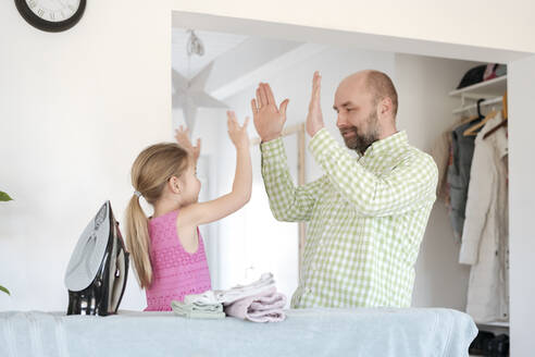 Father and daughter high fiving after ironing at home - VYF00107