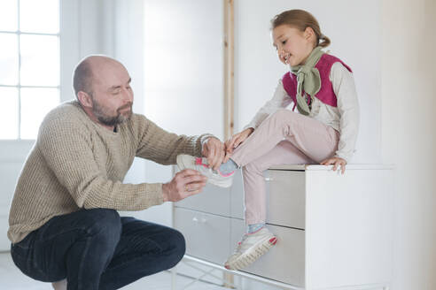 Father helping daughter putting on shoes at home - VYF00110
