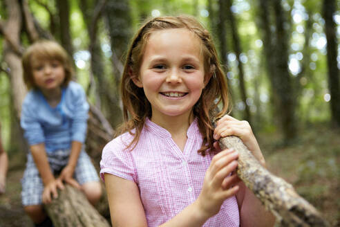 Portrait of smiling girl carrying log in forest - AUF00192