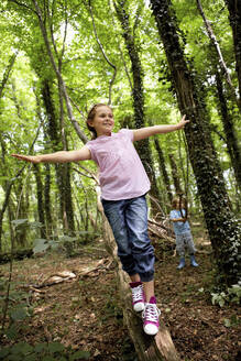 Girl balancing on log in forest - AUF00195