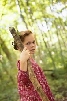 Portrait of girl with wood stick walking in forest - AUF00210