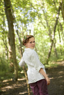 Portrait of girl with wood stick walking in forest - AUF00216