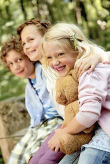 Happy children embracing in forest - AUF00222