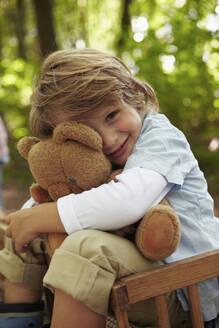 Portrait of boy hugging teddy bear in forest - AUF00225