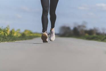 Female jogger on field path, waist down - CHPF00656