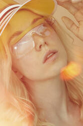 Portrait of young woman wearing glasses and sun visor - PGCF00073