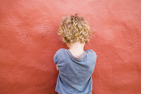 Back view of  little boy standing in front of red wall - IHF00301