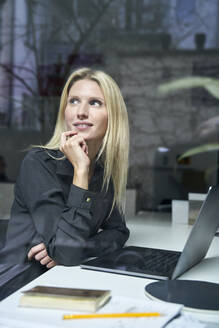 Portrait of smiling blond woman with laptop behind windowpane in office - PNEF02497