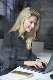 Smiling blond woman using laptop behind windowpane in office - PNEF02500