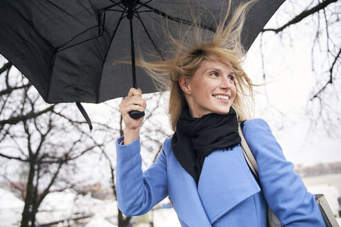 Smiling blond woman holding umbrella in storm - PNEF02503