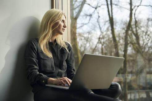 Blond woman sitting at the window using laptop - PNEF02512
