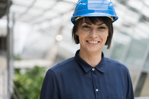 Female architect wearing blue hard hat, portrait - JOSEF00230
