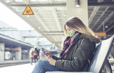 Young woman with smartphone wearing mask at station platform - BFRF02205