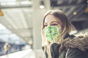 Portrait of young woman wearing mask at station platform - BFRF02208