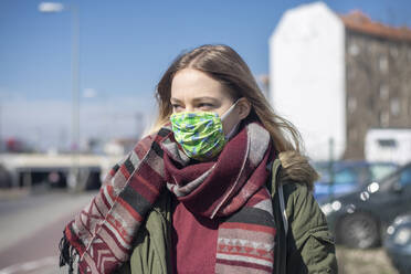 Portrait of young woman wearing mask in the city - BFRF02211