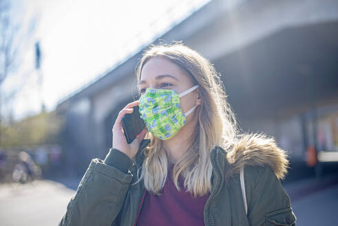 Portrait of young woman wearing mask and talking on the phone in the city - BFRF02214