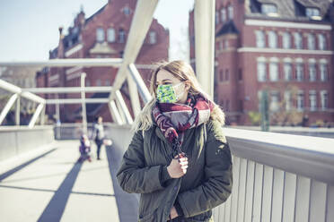 Portrait of young woman wearing mask on a bridge in the city - BFRF02217