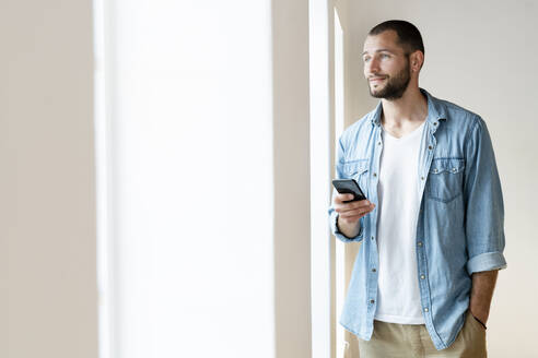 Smiling young man at home holding his smartphone while looking out of his window - SBOF02154