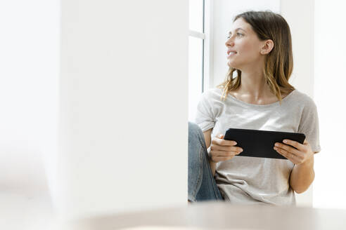 Young brunette woman at home sitting on window bench and looking outside while holding her tablet - SBOF02163