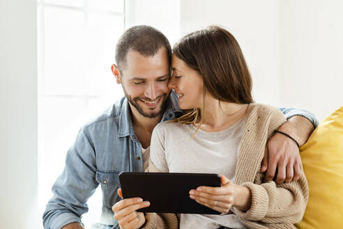 Happy affectionate couple with tablet at home - SBOF02181