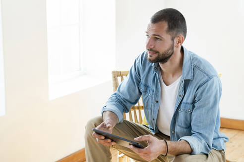 Young man at home sitting in wooden armchair in front of window holding tablet - SBOF02187