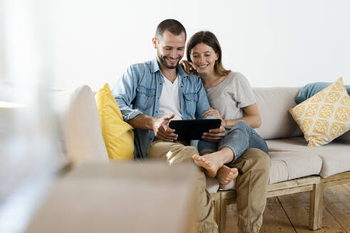 Happy couple at home in modern living room sitting on couch while looking at tablet together - SBOF02190