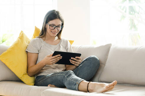 Smiling brunette woman with glasses relaxing on couch and looking at her tablet - SBOF02193