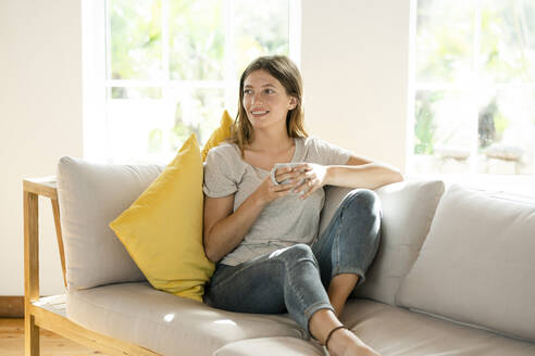 Smiling young woman relaxing on couch at home holding coffee mug - SBOF02199
