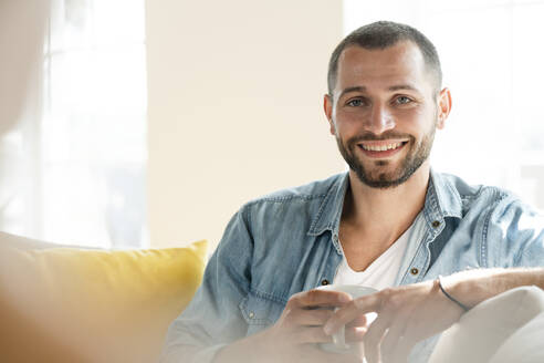 Portrait of happy young man at home holding coffee mug - SBOF02202