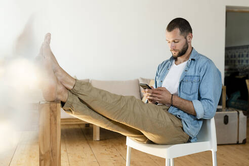 Young man at home typing on his smartphone in modern living room with his feet on the table - SBOF02214