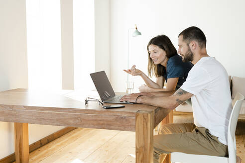 Young couple working at laptop from home in home office in modern living room - SBOF02220