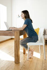 Young woman working at laptop from home in home office in modern living room - SBOF02226