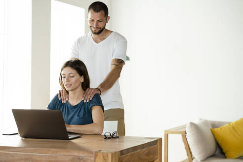 Woman working on laptop while boyfriend massaging her neck at home - SBOF02232
