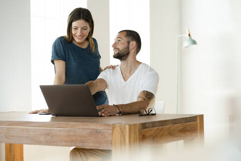 Smiling couple working at laptop from home in home office in modern living room - SBOF02235