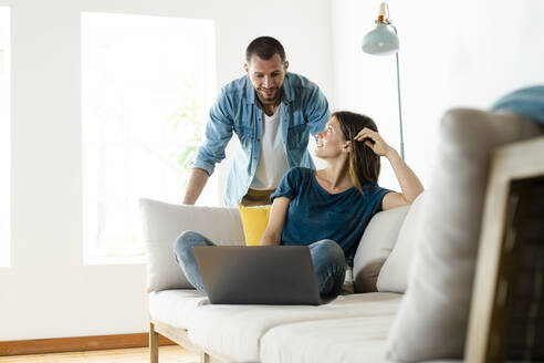Young couple on couch at home with laptop - SBOF02244