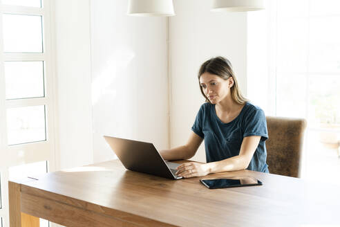 Young woman at home working on her laptop in home office - SBOF02253