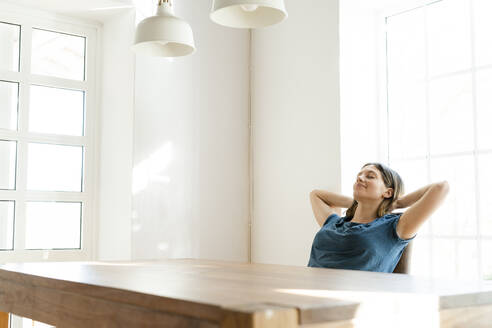 Young woman at table at home relaxing - SBOF02256