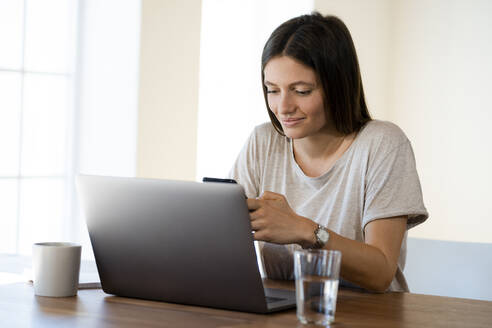 Smiling young woman at home with laptop checking her smartphone in home office - SBOF02268