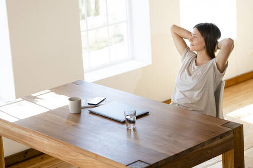 Young woman at home sitting at table in home office having a break - SBOF02271