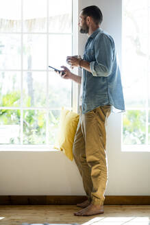 Young man at home holding his smartphone and coffee mug and looking outside - SBOF02274
