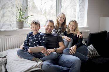 Portrait of happy family relaxing on couch at home - HMEF00842