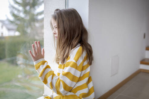Girl at home looking out of window - HMEF00854