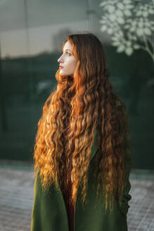 Portrait of pensive redheaded young woman looking at distance - TCEF00331